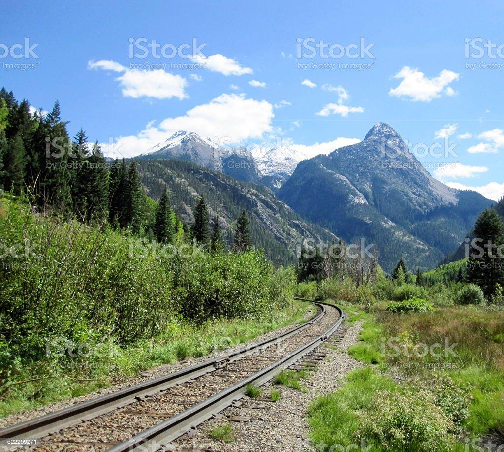 Railroad tracks through the San Juan Mountains towards a peak stock photo