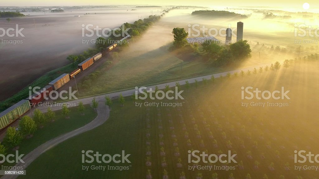 Railroad train rolls across breathtakingly beautiful, foggy landscape at sunrise stock photo