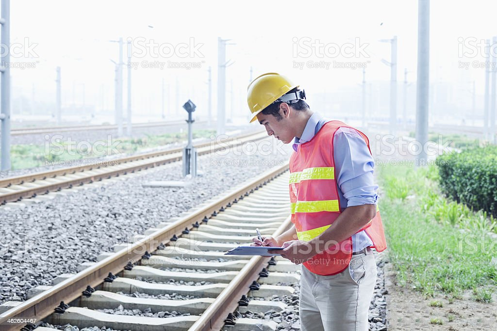 Railroad worker in protective work wear checking the tracks stock photo