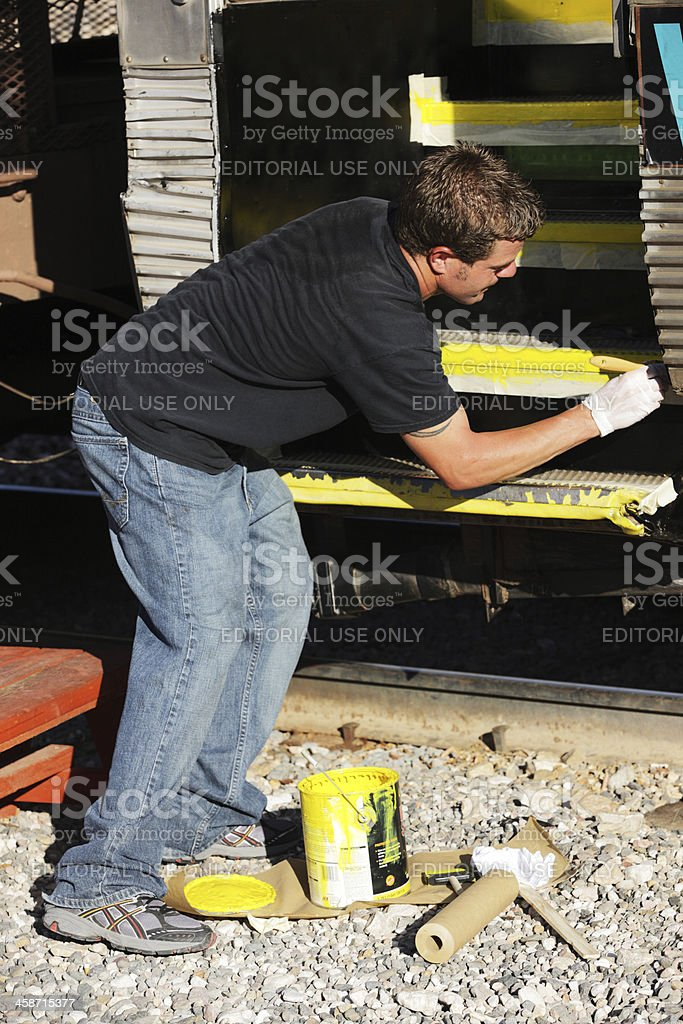 Railroad Worker Painting Train Car stock photo