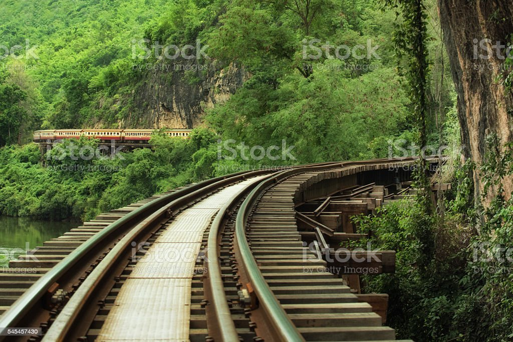 Rails in the forest along the cliffs stock photo
