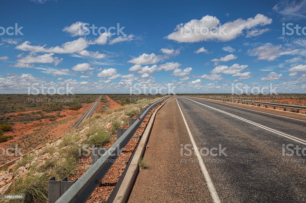 Railway and road in red bush in center Australia stock photo
