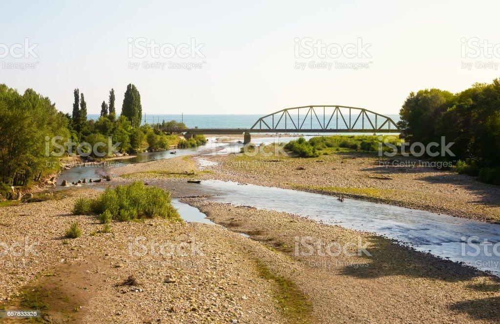 Railway bridge across the river, flowing into the sea stock photo