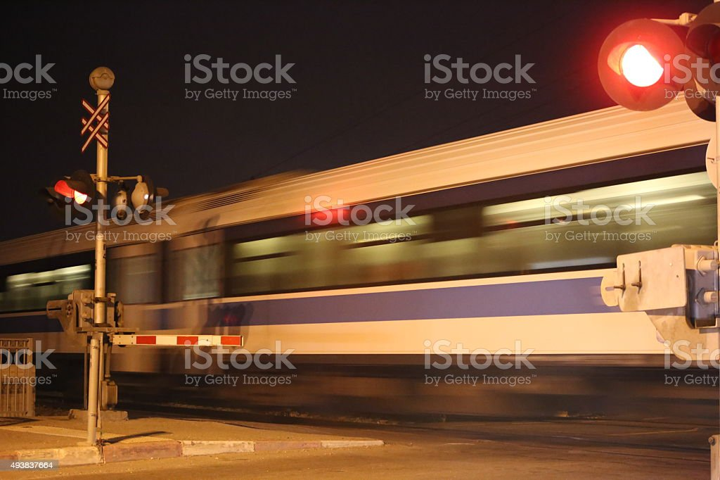 Railway Crossing by Night with Passing Train stock photo