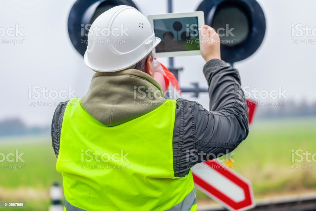 Railway engineer with tablet PC near the railway stock photo