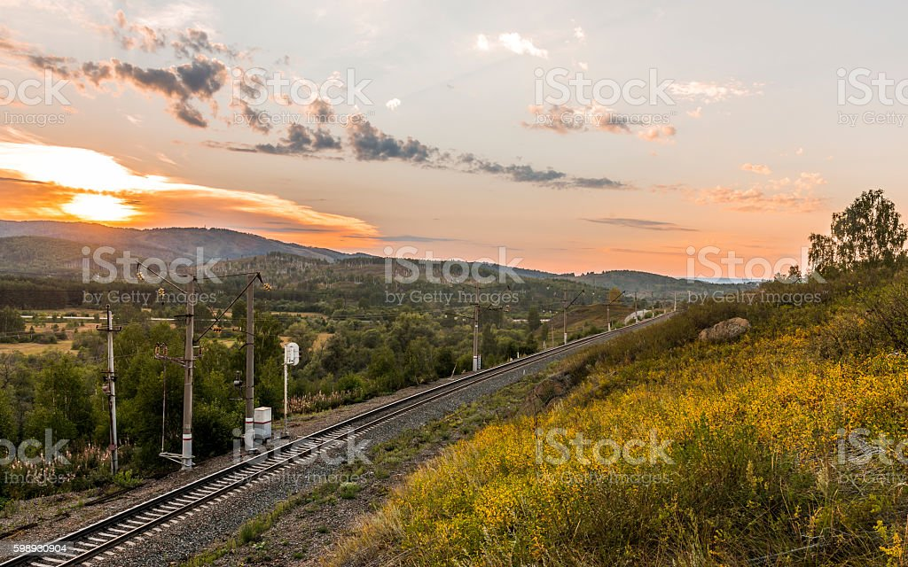 Railway in the mountains at sunset. stock photo