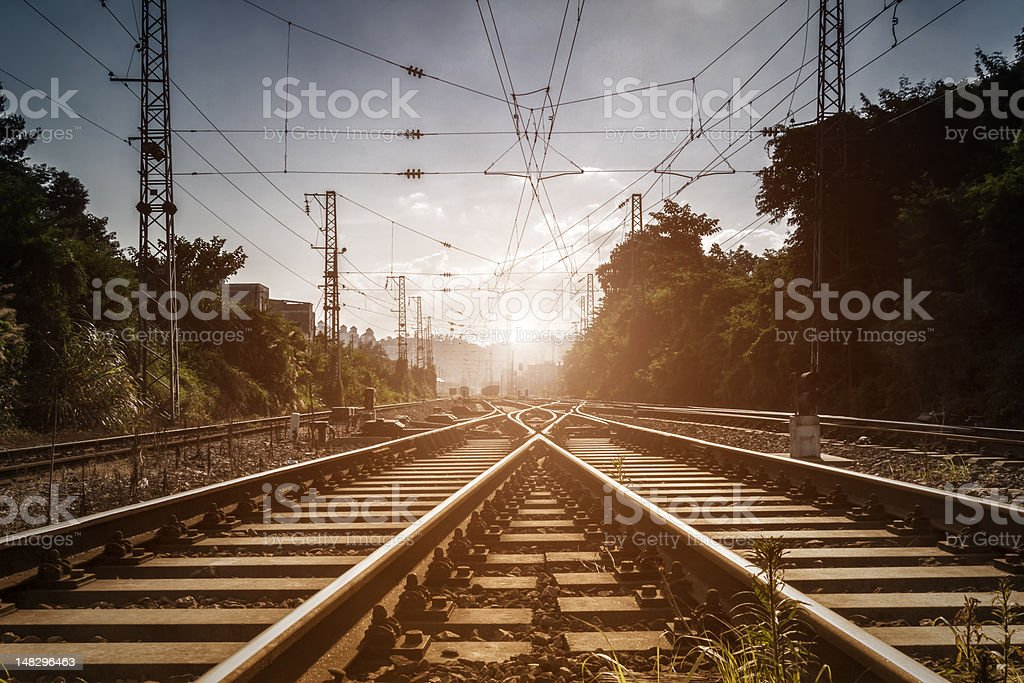 Railway lines leading into the distance and sunlight stock photo