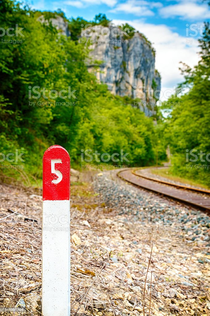Railway pole sign close-up with number five along railroad track stock photo