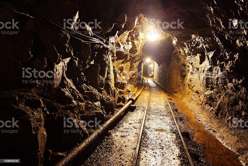 Railway running through dimly lit mine shaft stock photo
