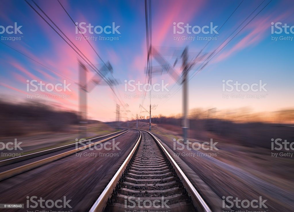 Railway station at colorful sunset with motion blur effect. Railroad stock photo