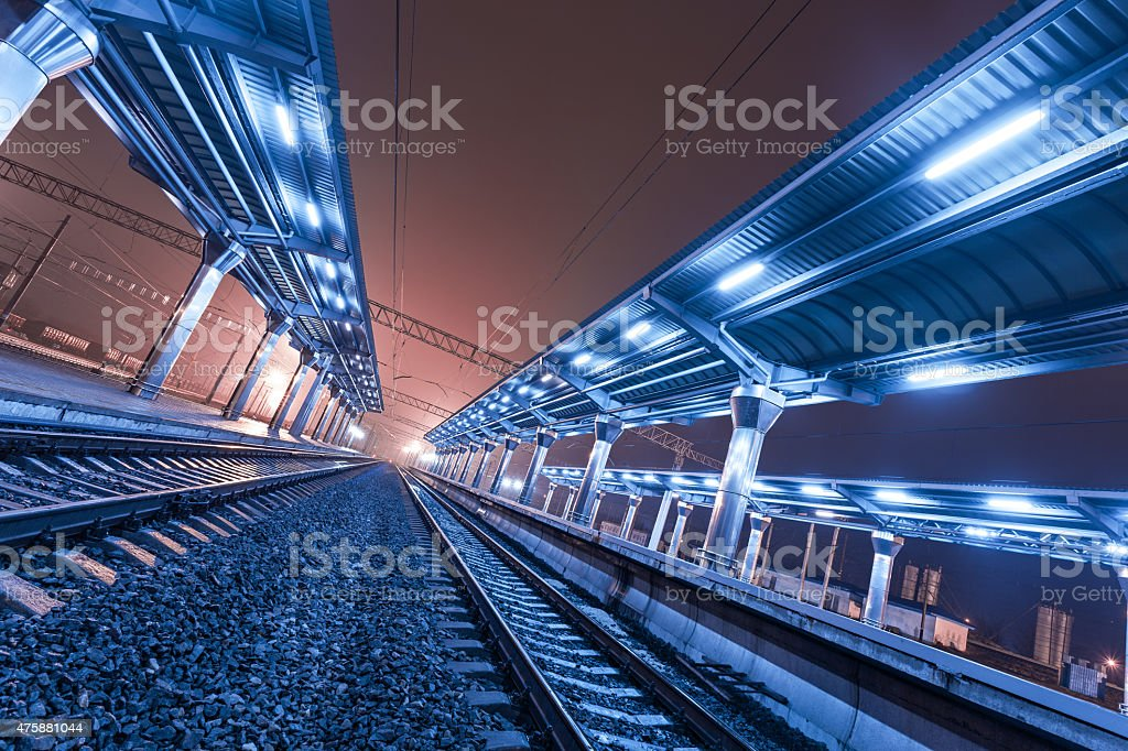 Railway station at night. Train platform in fog. Railroad stock photo