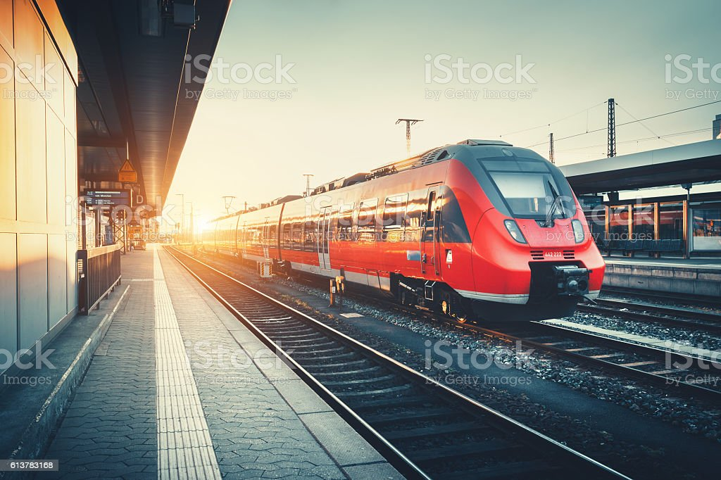 Railway station with beautiful modern red commuter train at suns stock photo
