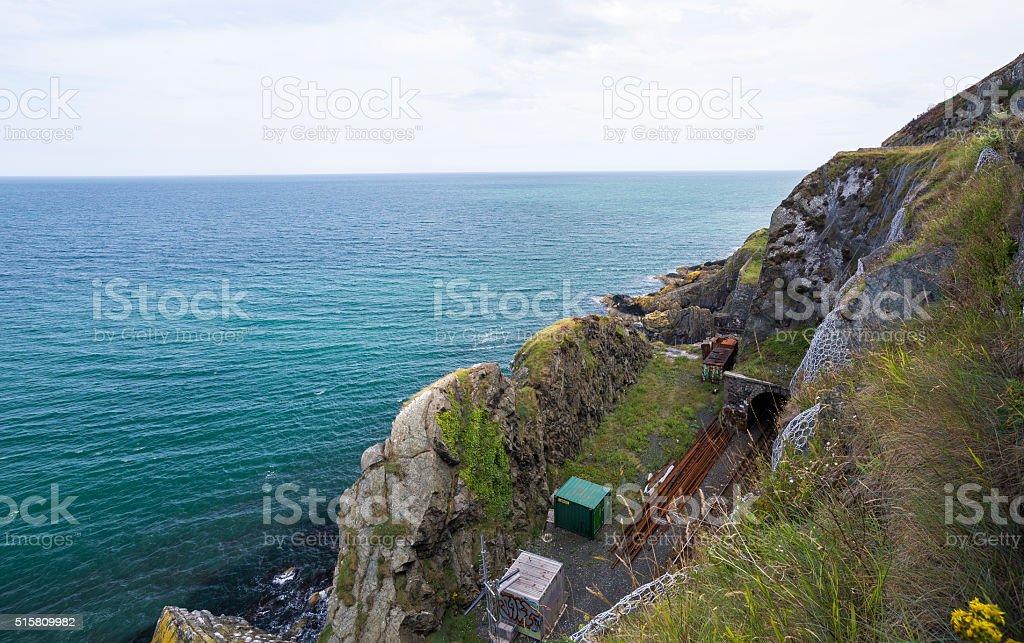 Railway through stone rocks mountain at Irish seacoast. Bray, Greystone stock photo