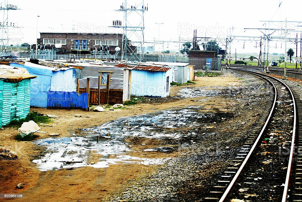 Railway track next to shacks stock photo
