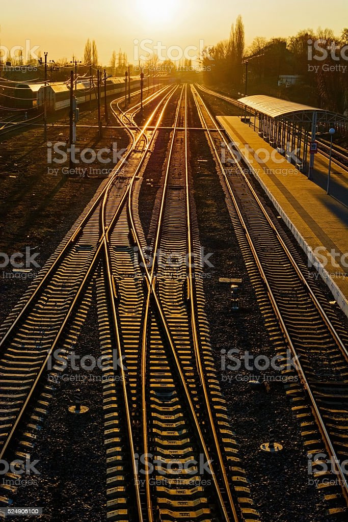 Railway Tracks at the train station at sunset. stock photo