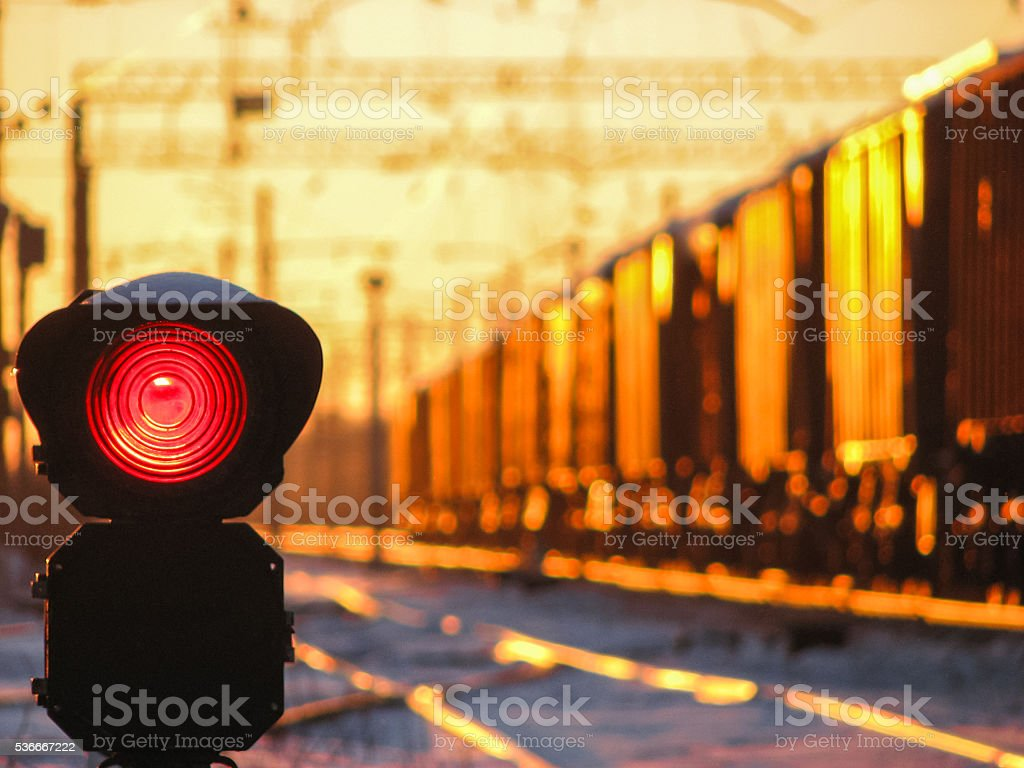 Railway traffic light at sunset shows red signal on railway stock photo