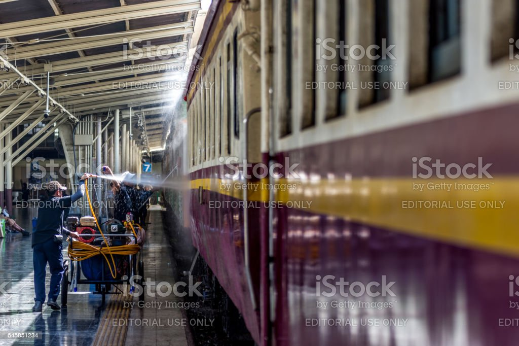 Railway train on the railroad tracks get a washing for cleaning by worker in Bangkok station. People popular travel by train because it is cheaper. stock photo