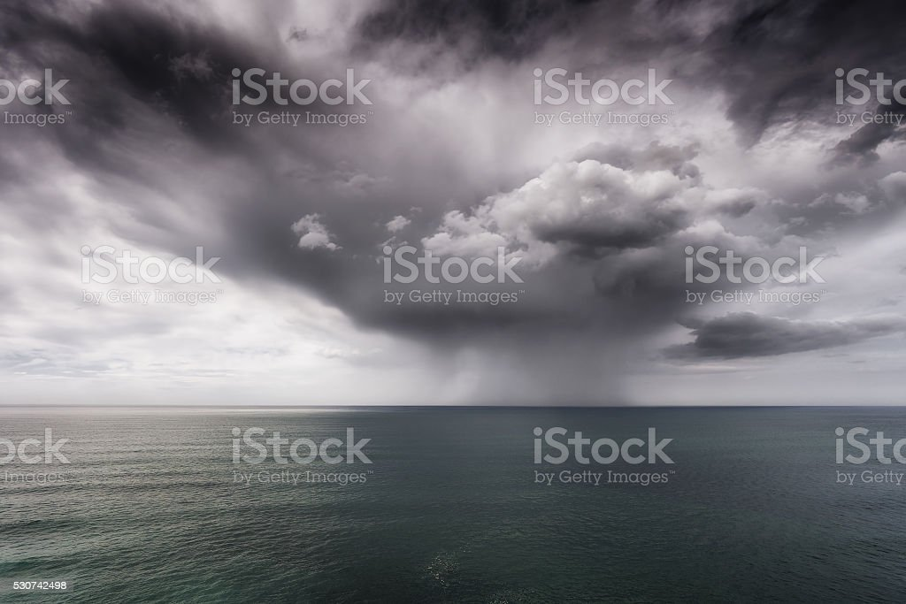 rain and stormy cloud over sea stock photo