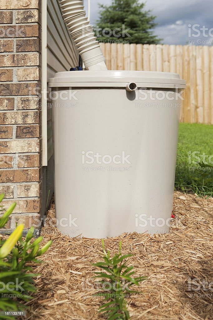 Rain Barrel next to House with Downspout stock photo
