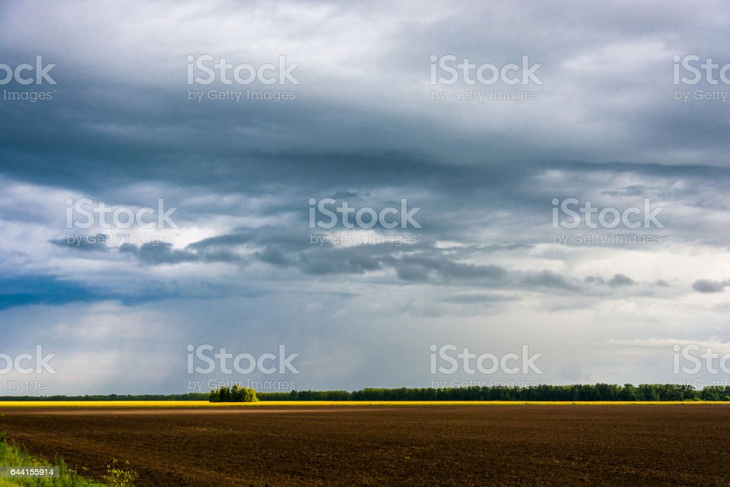 Rain clouds and plowed field. stock photo