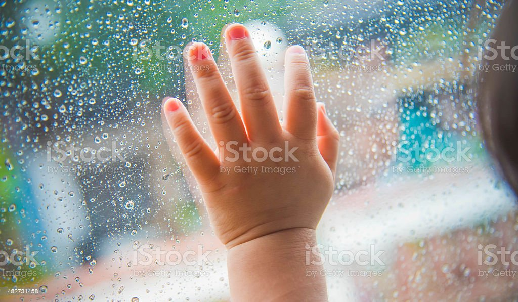 Rain drops on the car window and children hand . stock photo