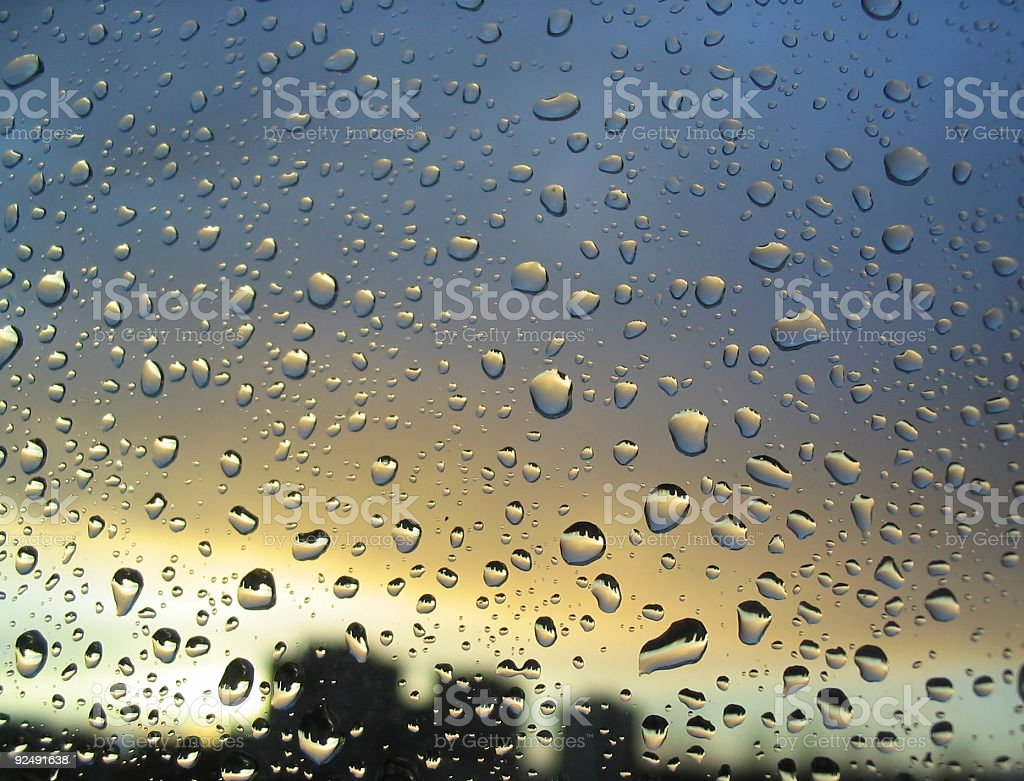 rain drops on the window, sunset in background, royalty-free stock photo
