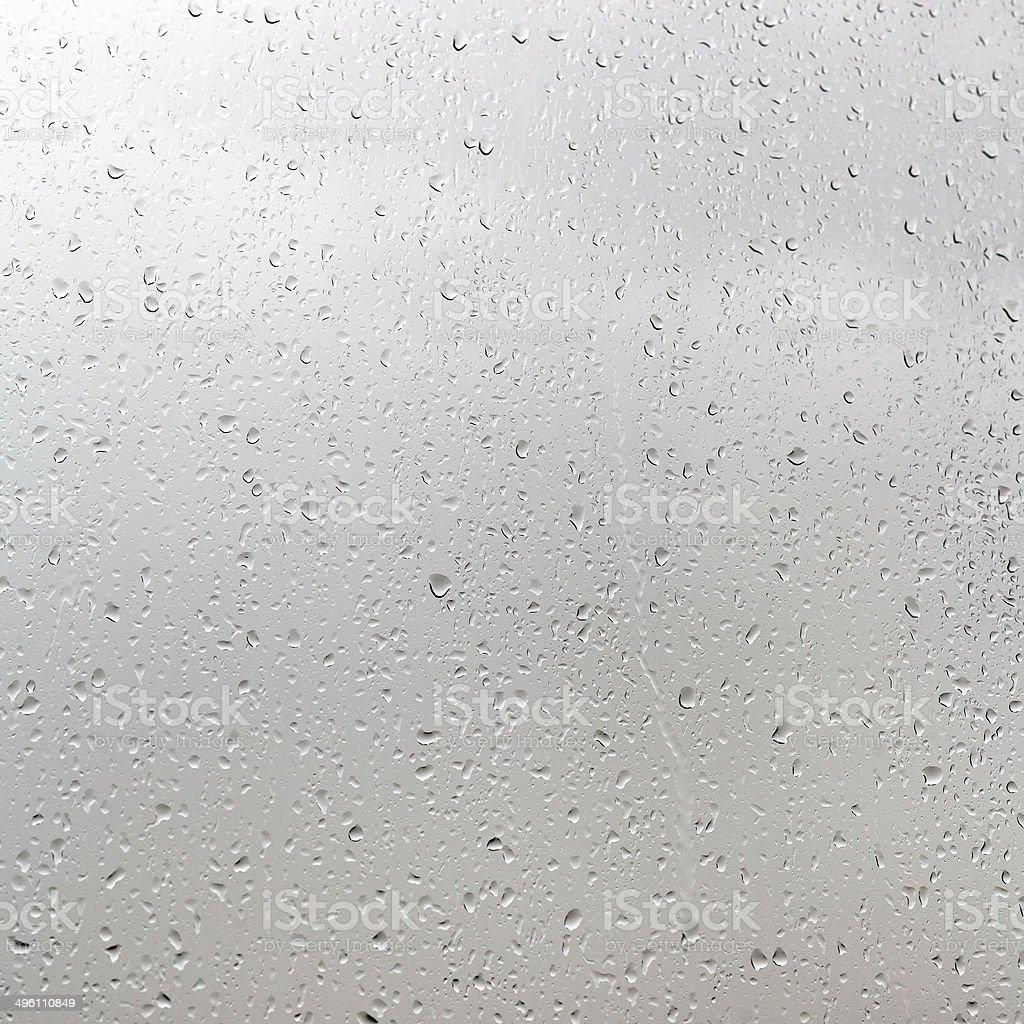rain drops on window pane in cloudy day stock photo