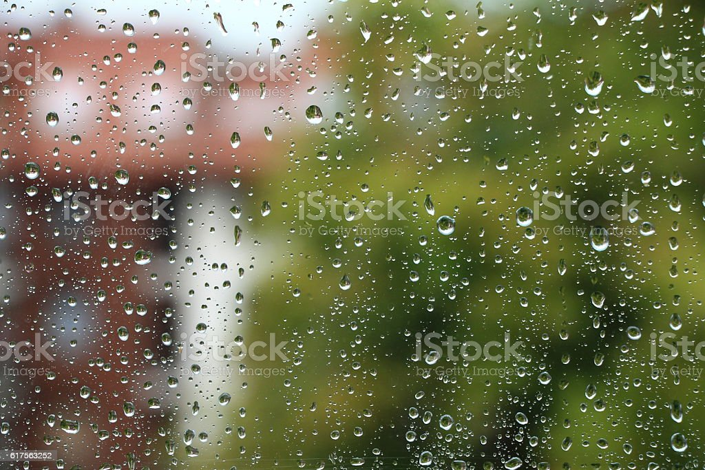 Rain drops on window with building in background stock photo