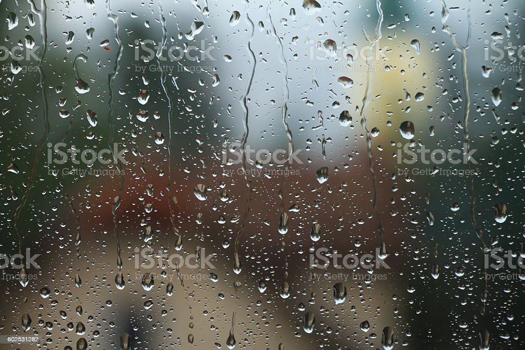 Rain drops on window with house and church in background stock photo
