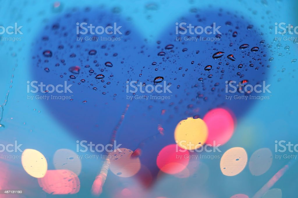 Rain drops on window with light bokeh and heart frame. stock photo