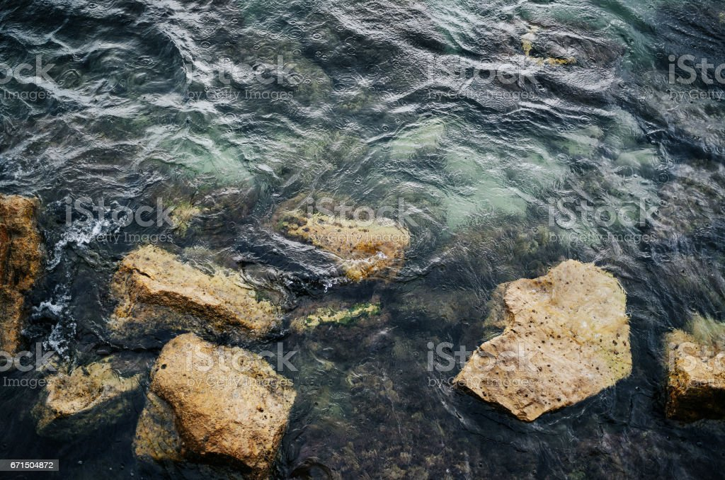 Rain drops ripples in the sea with rocks. Background pattern texture. stock photo