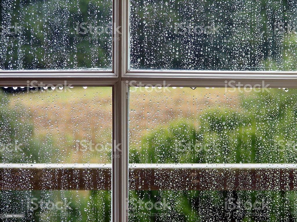 Rain drops rolling down four-paned window stock photo