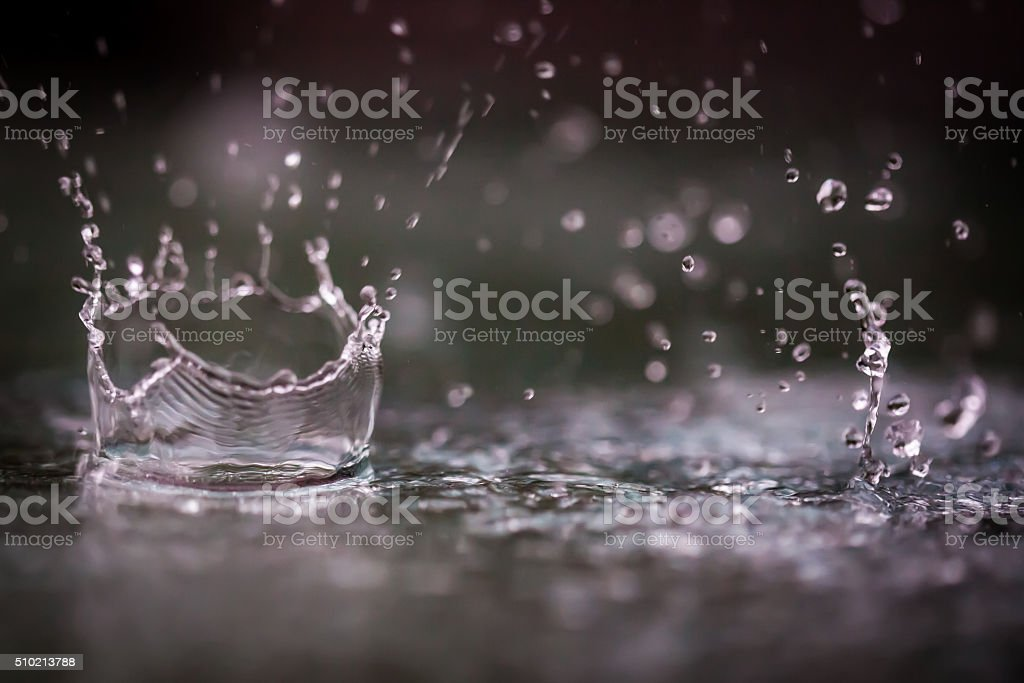 Rain drops splashing into a puddle of water. stock photo