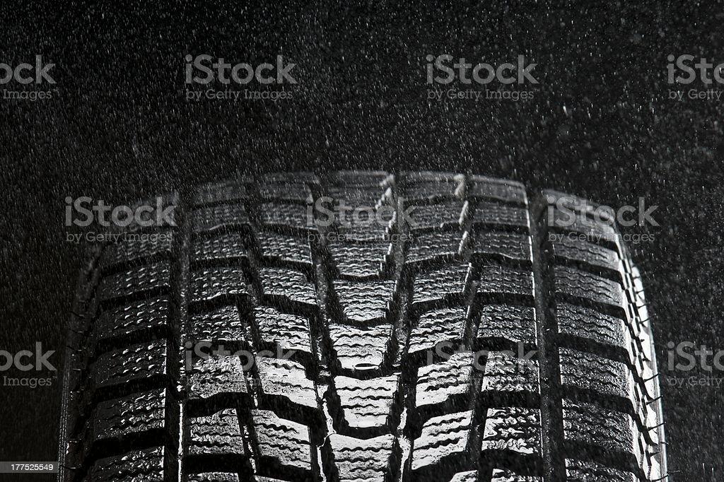 rain falling over tire tread detail stock photo