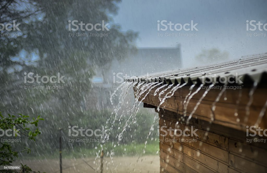 rain flows down from a roof down stock photo