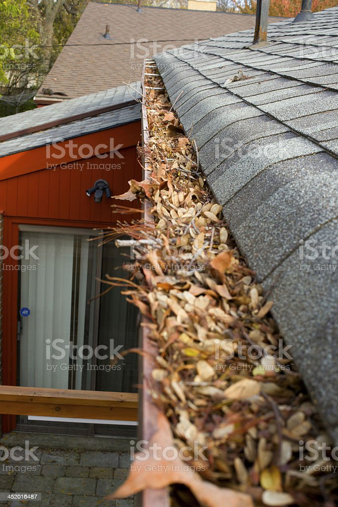 Rain gutter on roof filled with leaves stock photo