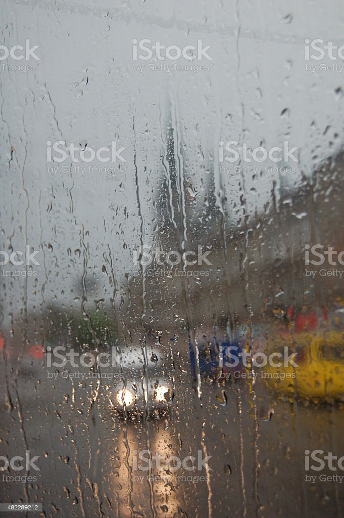 Rain in the evening city. Drops, flows and lanterns. stock photo
