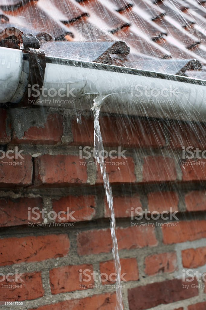 rain pouring down on tiled roof with leaking gutter