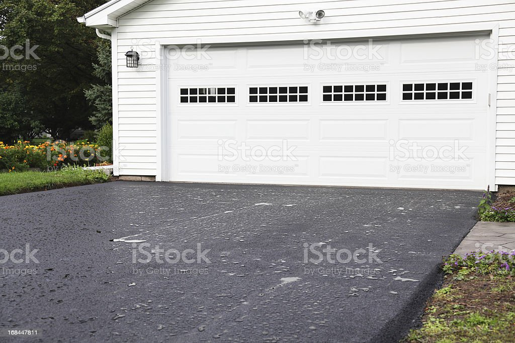 Rain Puddles on New Asphalt Driveway at Residential Home stock photo