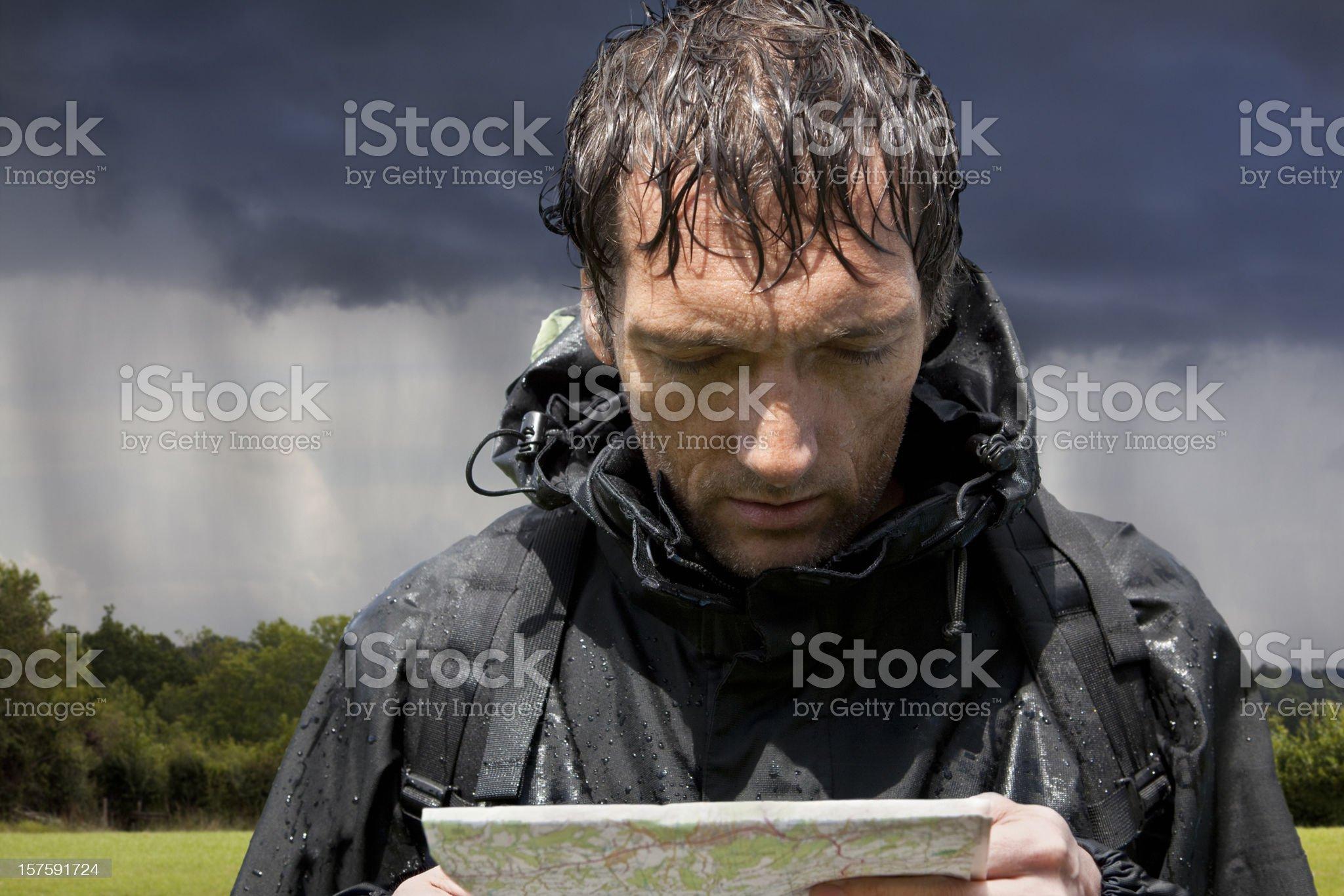 Rain Soaked Hiker Looking at Map royalty-free stock photo