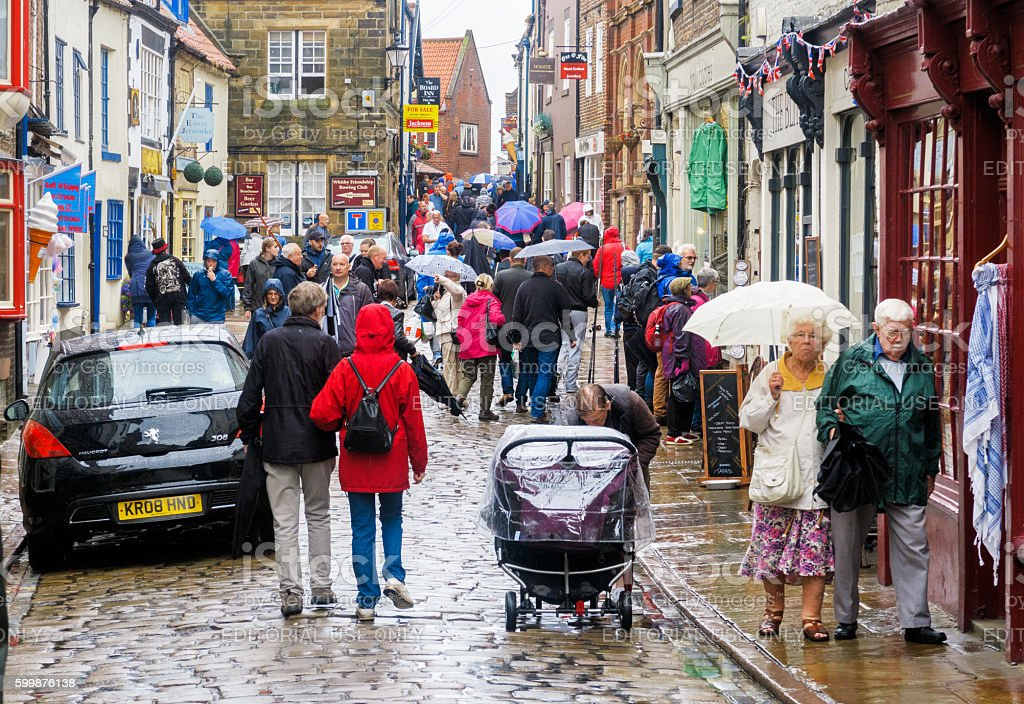 Rain soaked tourists, Church Street, Whitby. stock photo