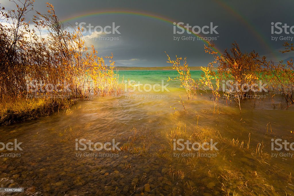 Rainbow and dark clouds over large lake royalty-free stock photo