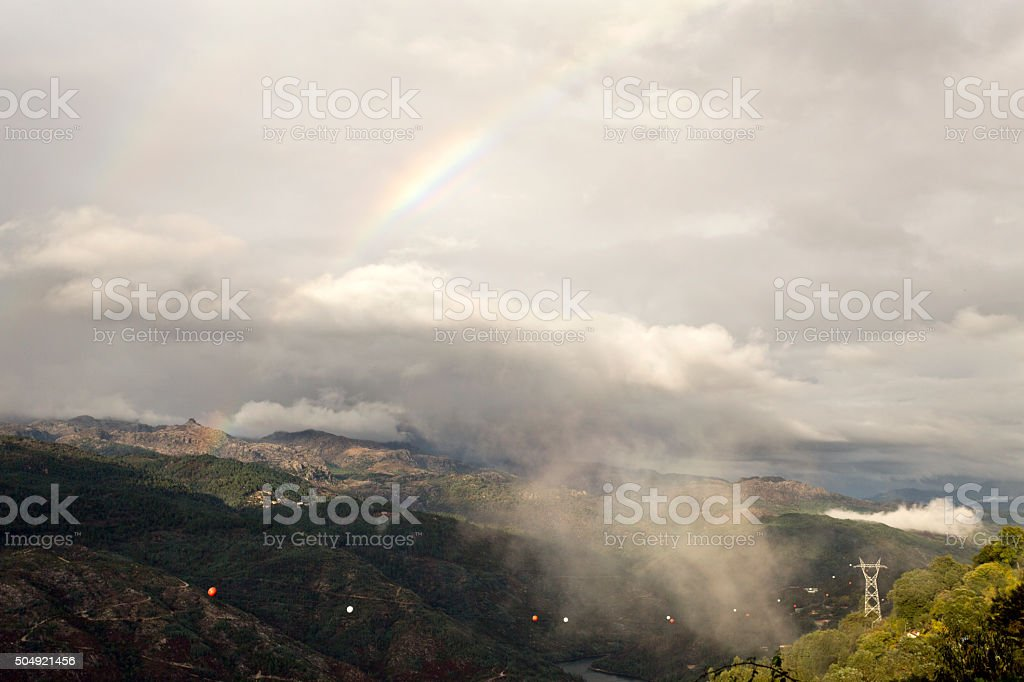 Rainbow and Low Cloud on the Valley stock photo