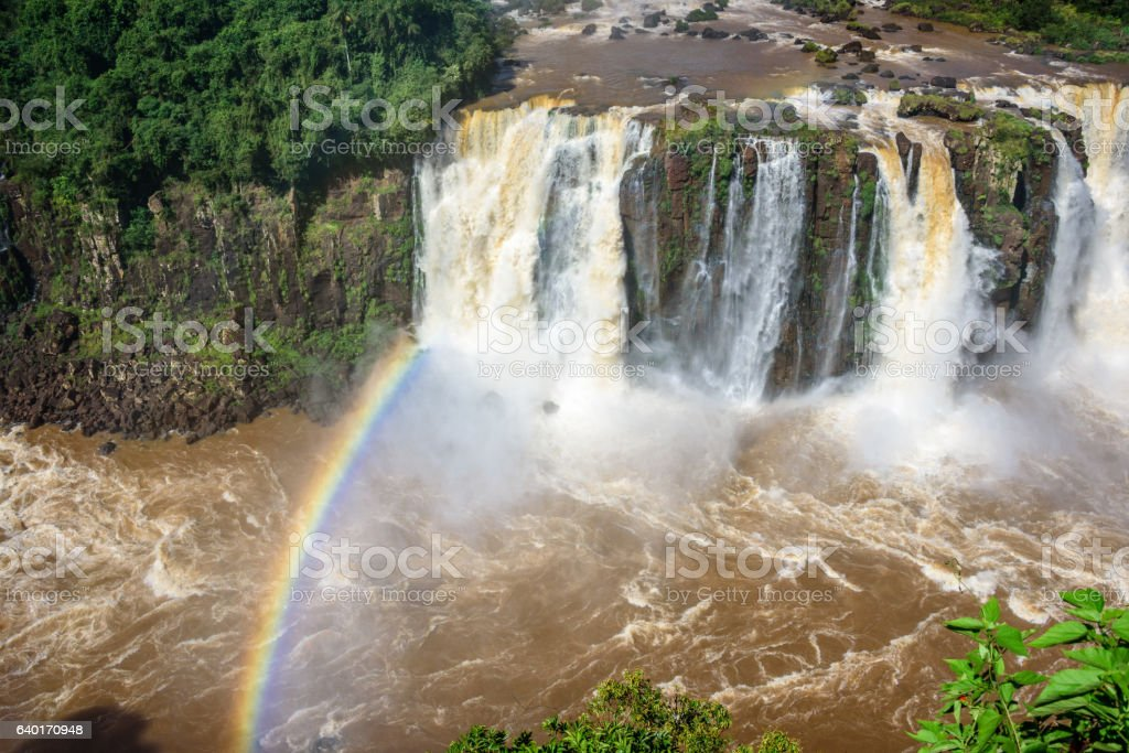 Rainbow and view of cascading water of Iguazu Falls stock photo