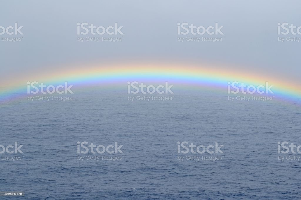 Rainbow at sea showing gentle curve and waves. stock photo