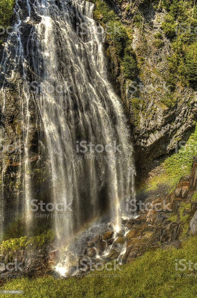 Rainbow at the bottom of waterfall stock photo