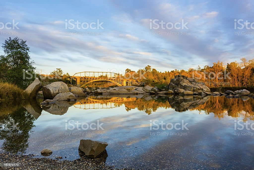 Rainbow bridge and clouds reflecting in the water stock photo
