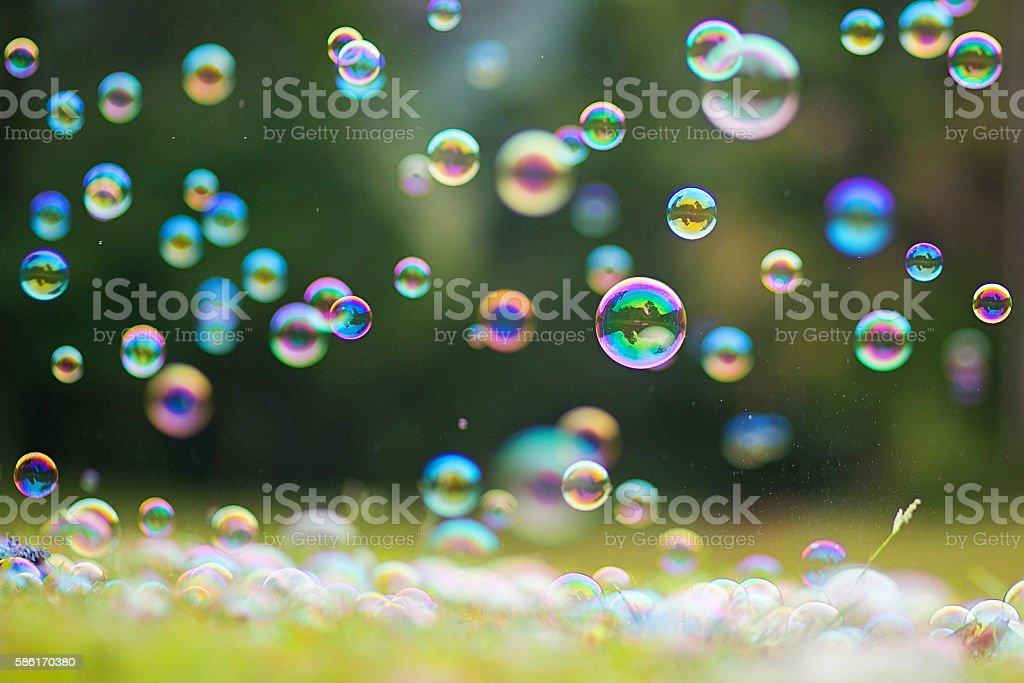 Rainbow bubbles on grass background. stock photo