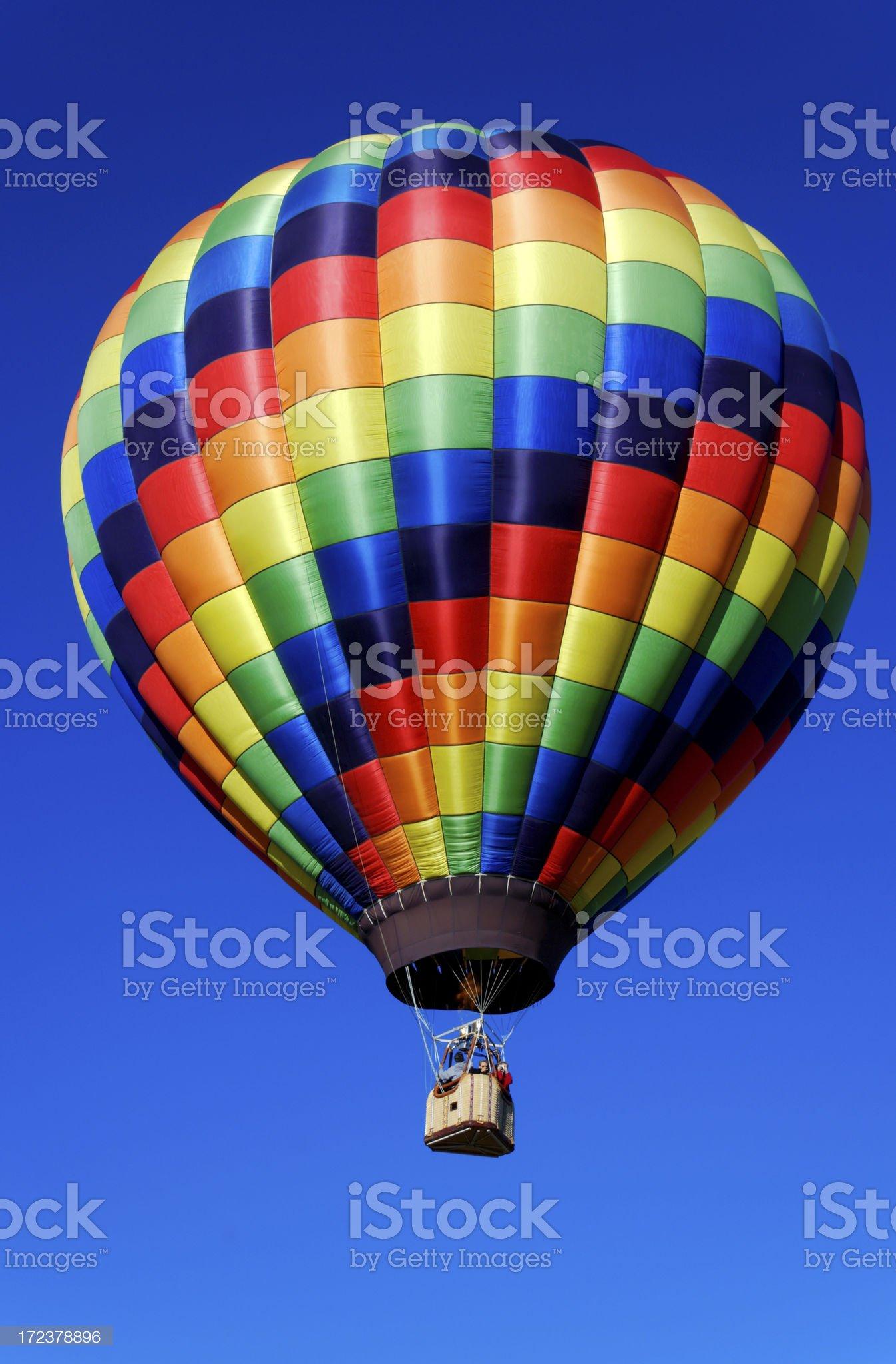 Rainbow Checkered Hot Air Balloon on a Clear Blue Sky royalty-free stock photo