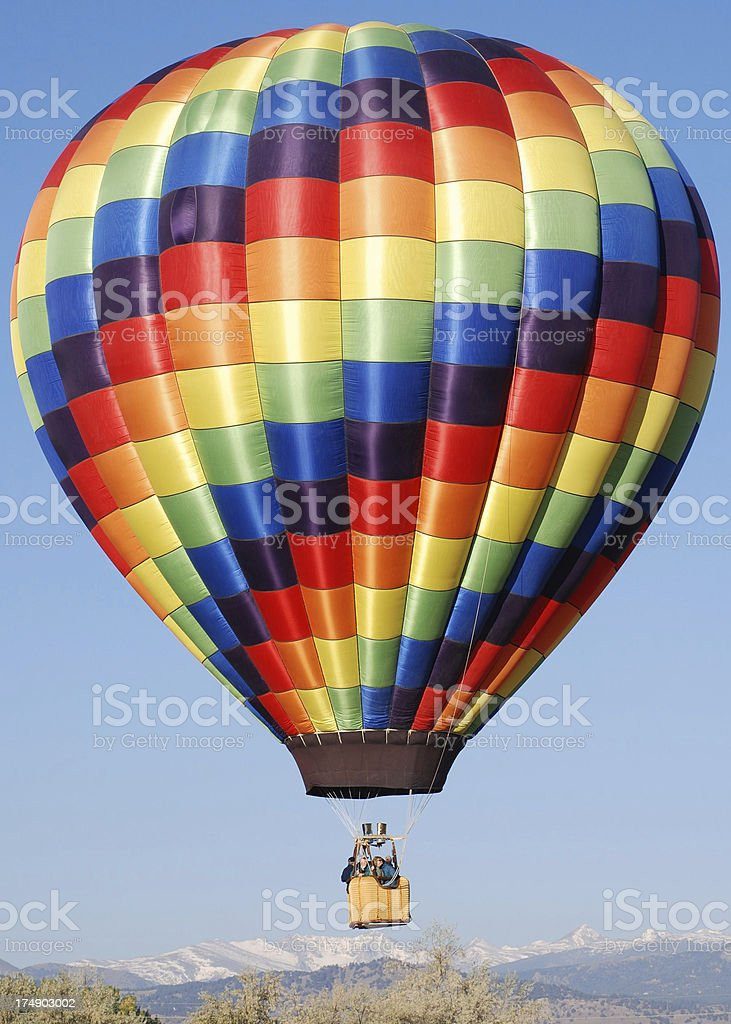 Rainbow Checkered Hot Air Balloon over Mountains royalty-free stock photo